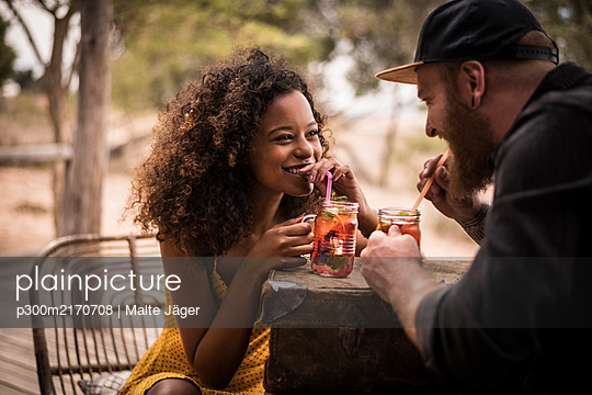 Happy couple drinking fresh ice tea drinks together - p300m2170708 by Malte Jäger