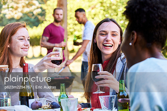 Smiling young women having wine and beer in park - p623m2294767 by Eric Audras