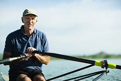 A middle-aged man rowing a single scull rowing boat on the water.  - p1100m876298f by Jamie Kripke
