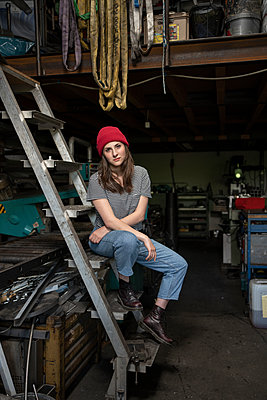 Young woman in red knit cap in a workshop - p1437m2253423 by Achim Bunz