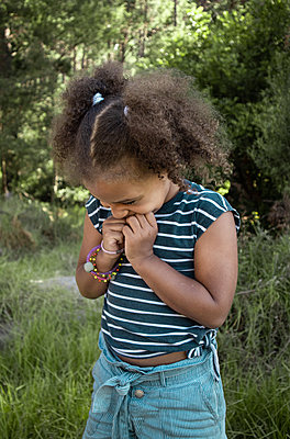 Curly-haired little girl in the countryside - p1640m2246791 by Holly & John