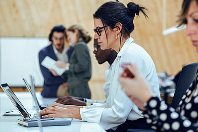 Businesswoman using laptop while sitting amidst colleagues in coworking office - p300m2256034 by Josep Suria