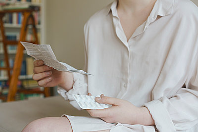 Midsection of woman reading prescription of pills at home - p301m1148180 by Halfdark