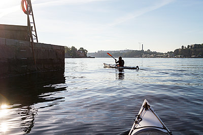 Person kayaking on sea - p312m1103736f by Henrik Trygg