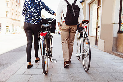 Low section rear view of business colleagues walking with bicycles on sidewalk - p426m1196693 by Maskot