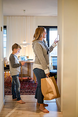 Mother with shopping bag using digital tablet on wall while son standing at home - p426m2195133 by Maskot
