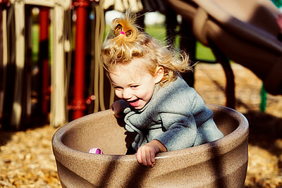 A cute young girl spinning in a saucer on a playground during the fall season; Spruce Grove, Alberta, Canada - p442m2004264 by LJM Photo