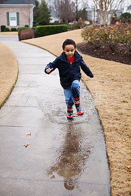 Mixed race boy splashing in rainboots - p555m1454235 by Roberto Westbrook