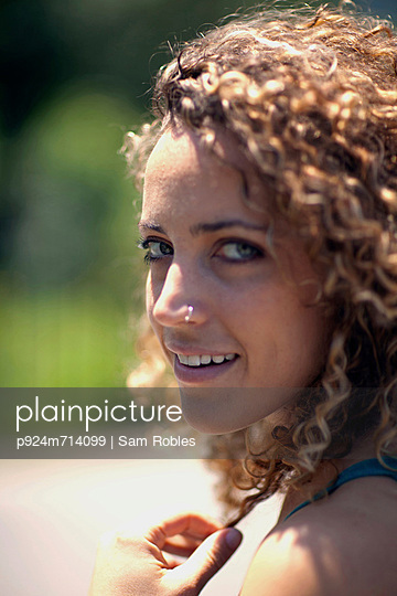 Woman with curly hair and nose ring, close up - p924m714099 by Sam Robles