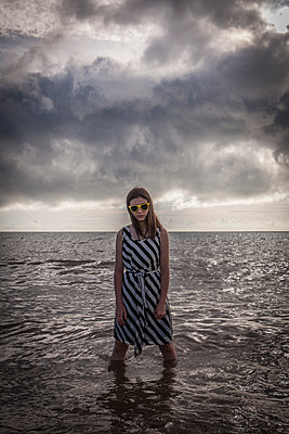 Girl with sunglasses standing in the sea - p1402m2248676 by Jerome Paressant