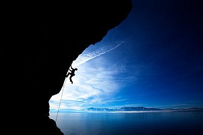 Man climbing against blue sky. - p1424m1501108 by Corey Rich