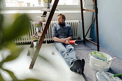 Man renovating room sitting on the floor having a rest - p300m1581175 von Joseffson