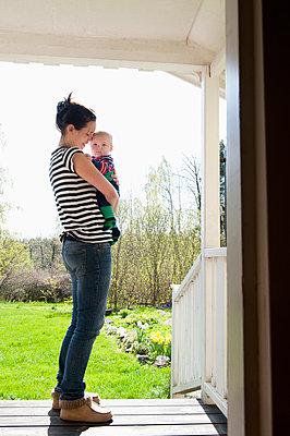 Sweden, Ostergotland, Vikbolandet, Woman carrying baby boy (6-11 months) - p352m1126610f by Julia Sjöberg