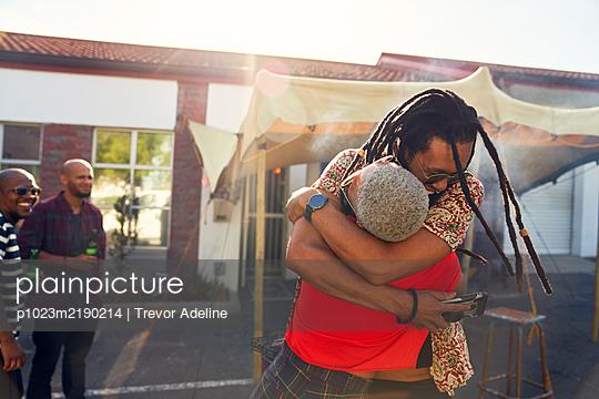 Happy friends hugging in sunny parking lot - p1023m2190214 by Trevor Adeline