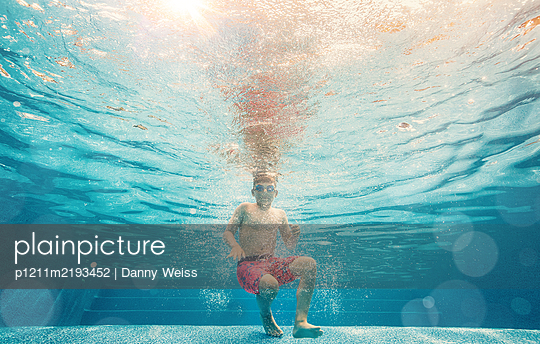 Boy underwater in the pool - p1211m2193452 by Danny Weiss