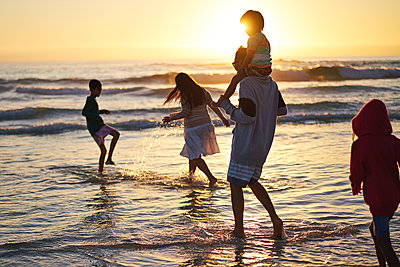 Family playing and splashing in ocean surf at sunset - p1023m2200838 by Trevor Adeline