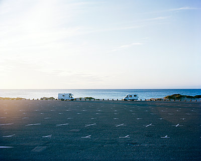 Denmark, Tisvilde, View to parking lot with two winnebego parked for night - p352m1187417 by Lauri Rotko