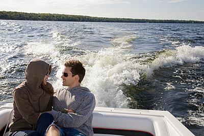Couple sitting in speedboat on lake - p4296254 by Hugh Whitaker