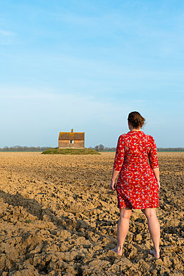 Woman and deserted house in a polder, rear view, Dordrecht, South Holland, Netherlands, Europe - p429m1513644 by Mischa Keijser