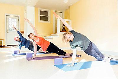 Three women practicing yoga pose in yoga studio - p429m1578388 by Ashley Corbin-Teich