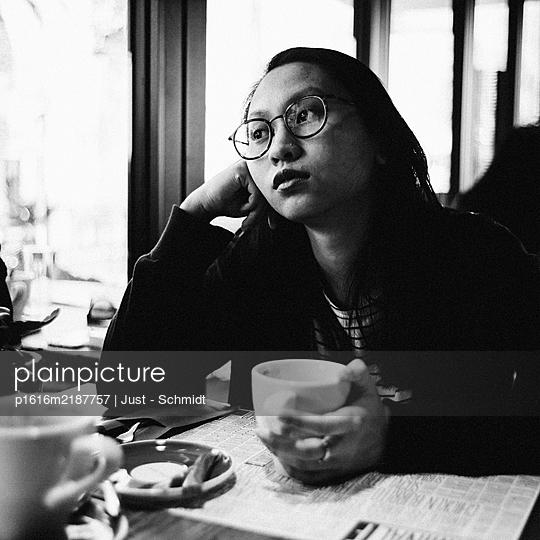 Asian Woman in a Cafe, portrait - p1616m2187757 by Just - Schmidt