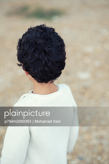 Rear view of little boy standing outdoors  - p794m2260353 by Mohamad Itani