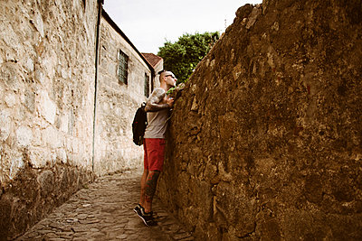 Side view of man with backpack standing by retaining wall at alley - p1166m2024847 by Cavan Images