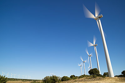 Low angle view of windmills spinning on field against clear blue sky - p1166m2040511 by Cavan Images