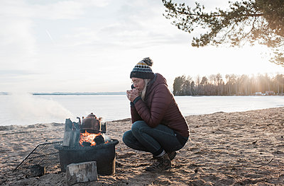 woman warming up sat next to a camp fire on an empty beach in Sweden - p1166m2171484 by Cavan Images