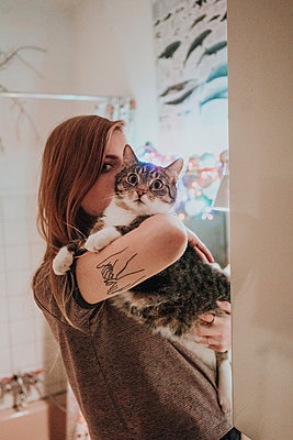 Young woman carries tabby tomcat in her arms  - p1184m1424466 by brabanski