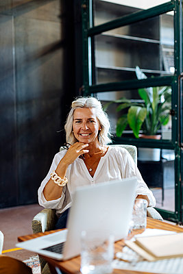Portrait of smiling mature businesswoman with laptop in loft office - p300m2144834 by Sofie Delauw