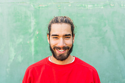 Portrait of bearded young man wearing red sweatshirt in front of green wall - p300m2159950 by VITTA GALLERY