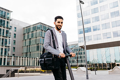Portrait of casual young businessman with electric scooter in the city - p300m2160166 by Josep Rovirosa