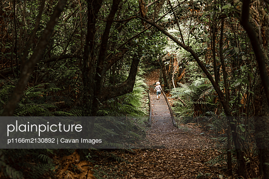 Toddler boy running on wooden path in a lush forest - p1166m2130892 by Cavan Images