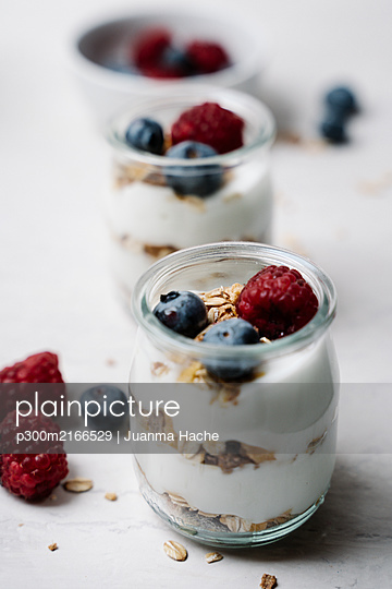 Small jars of granola with yogurt, blueberries and raspberries - p300m2166529 by Juanma Hache