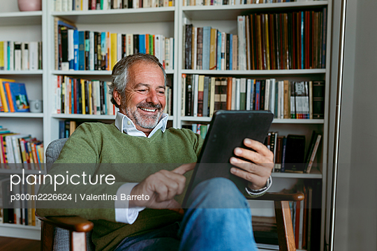 Smiling man using digital tablet while sitting against bookshelf at home - p300m2226624 by Valentina Barreto