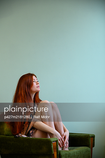 Red-haired woman sitting on armchair - p427m2181280 by Ralf Mohr
