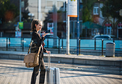 Smiling young woman with luggage at tram station in the city using cell phone - p300m2059607 von Uwe Umstätter