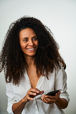 Smiling curly haired woman looking away while holding mobile phone against gray background - p300m2264574 by Annika List