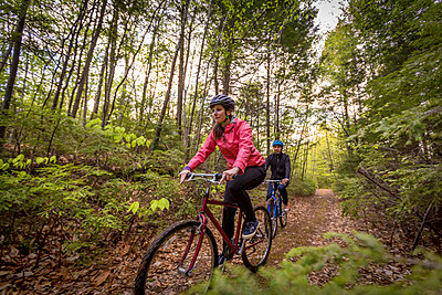 A couple mountain biking on a forest trail near Stonehouse Pond in Barrington, New Hampshire. - p343m1443418 by Jerry Monkman