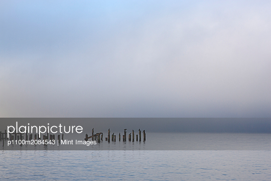 Wooden poles in ocean under cloudy sky,Edmonds, Washington, USA - p1100m2084543 by Mint Images