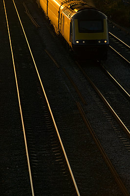 Rail lines lit by the late evening light as it reflects from the track - p1057m1475311 by Stephen Shepherd
