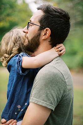 Little girl holding on to her fathers neck as he carries her - p1166m2216854 by Cavan Images