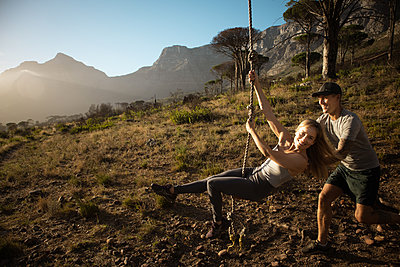 Man pushes woman on a swing - p1640m2260977 by Holly & John