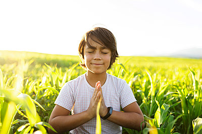 Smiling boy practicing yoga while sitting on grass in meadow - p300m2221730 by Valentina Barreto