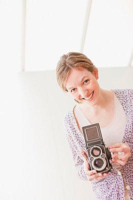 Smiling woman holding retro camera - p64114069f by Tom Merton