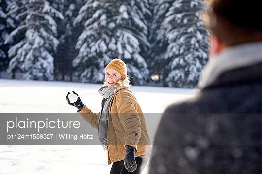 Junges Paar macht eine Schneeballschlacht - p1124m1589327 von Willing-Holtz