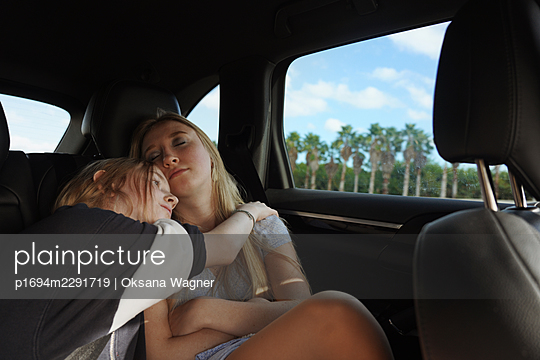 Two cute sisters cuddling in a car on a road trip  - p1694m2291719 by Oksana Wagner