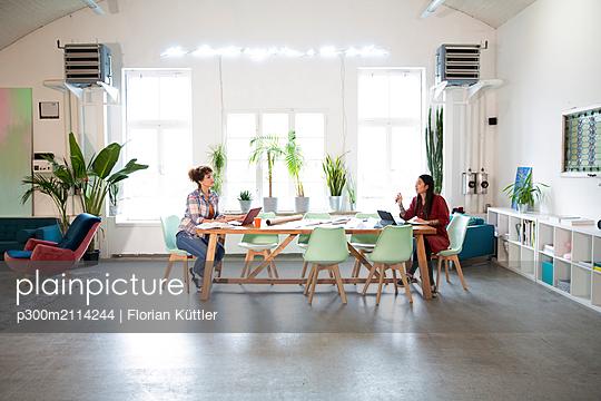 Two women working at table in modern office - p300m2114244 von Florian Küttler