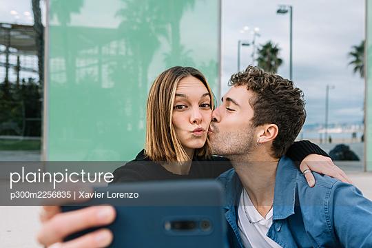 Smiling couple takingselfieoutdoors - p300m2256835 by Xavier Lorenzo